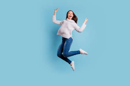Full length photo of content candid girl jump have free time make v-signs feel crazy, wear denim jeans white pullover white sneakers isolated over blue color background Фото со стока