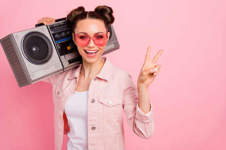 Close up photo of cheerful teen making v-signs holding boom box, wearing jacket isolated over pink background