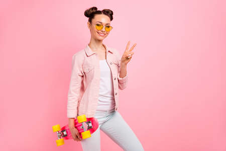 Portrait of cheerful lady making v-signs wearing jacket isolated over, pink background Фото со стока