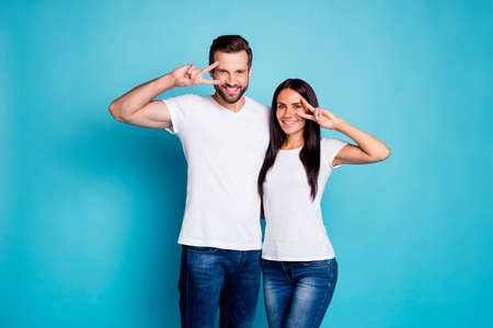 Photo of cute marriage pair showing v-sign symbols wear casual outfit isolated, blue background Фото со стока