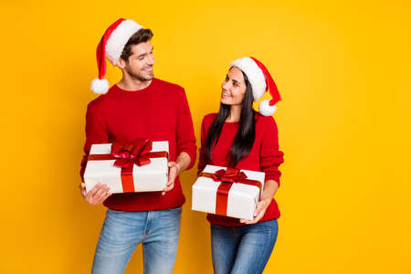 Portrait of positive married people with brown hair get packages wear red pullover denim jeans isolated over yellow background Foto de archivo