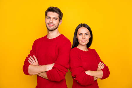 Portrait of focused man and woman with crossed hands stare wear red pullover isolated over yellow background