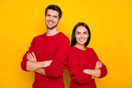 Portrait of cheerful couple with hands crossed wear red sweater isolated over yellow background