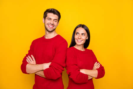 Portrait of charming spouses with crossed hands wear red pullover isolated over yellow background Stock Photo