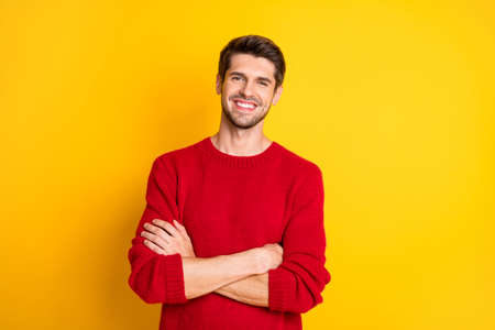 Portrait of charming man with his hands crossed wear red jumper isolated over yellow background Stock Photo