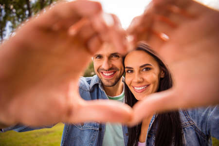 Close-up portrait of his he her she nice attractive cheerful tender winsome amorous married spouses tourists showing heart frame shape perfect match in green wood forest