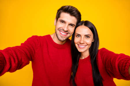 Close up photo of cheeerful spouses make self-portrait wear red sweater isolated over yellow background