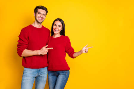 Portrait of charming spouses point at copy space recommend ads wear red pullover sweater denim jeans isolated over yellow background
