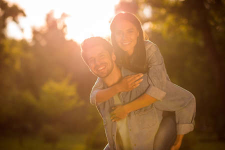 Close up photo of charming girl and guy piggyback standing in forest under sun wearing denim jeans jackets outside Stock Photo