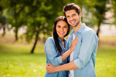 Foto eines Paares, das einen sonnigen Tag und einen Parkspaziergang genießt, trägt ein lässiges Denim-Outfit Standard-Bild