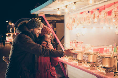Nice attractive charming lovely cheerful couple wearing warm outfit spending December winter vacation visiting international festival buying goods souvenirs things for family at street sale 版權商用圖片