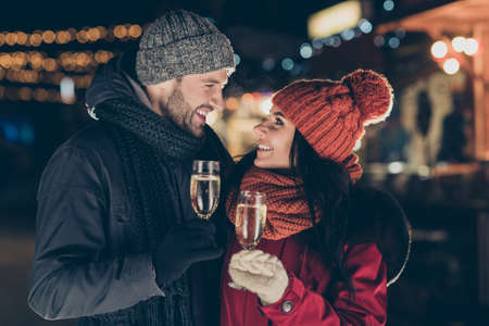 Close-up portrait of his he her she nice attractive lovely charming lovable affectionate cheerful cheery dreamy couple wearing warm outfit clinking glasses congrats midnight outdoor festive