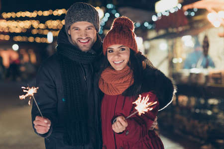 Photo of pretty couple at x-mas celebration in park holding magic sparklers at outdoors newyear party wearing warm coats knitted caps and scarfs