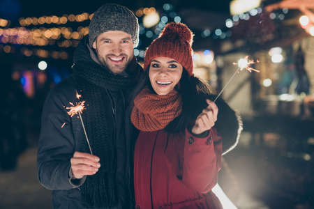 Photo of funny couple at x-mas celebration in park holding magic sparklers excited to meet newyear midnight wearing warm coats knitted caps and scarfs outdoors