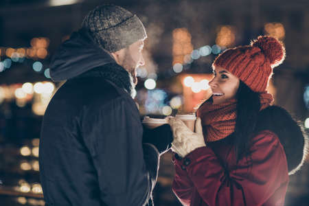 Photo of two people with hot tea beverage in hands spending x-mas evening at decorated park proposition moment wearing warm coats outside