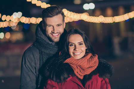 New year new love. Photo of two sweethearts pair outdoors hugging piggyback at newyear evening wearing warm winter jackets