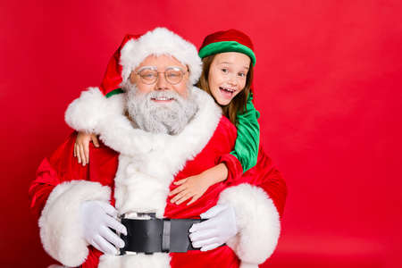 Close up photo of charming santa claus in eyeglasses eyewear and his little elf helper in green hat headwear hugging piggyback isolated over red background