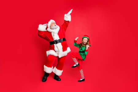 Full size photo of excited two people santa claus elf dancing enjoying midnight party wearing eyeglasses eyewear hat headwear spectacles isolated over red background Standard-Bild - 130568230