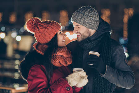 Photo of two affectionate people with hot tea beverage in hands celebrating x-mas eve in magic atmosphere wearing warm coats outside
