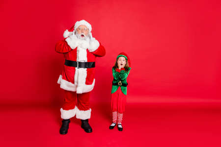 Full length photo of impressed santa claus elf in hat headwear with spectacles see christmas magic s scream omg touch faces isolated over red background Stockfoto