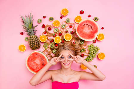 Vertical side profile top above high angle view photo beautiful she her lady lying down among different fruit slices show v-sign funny funky fingers near eyes healing complex isolated pink background