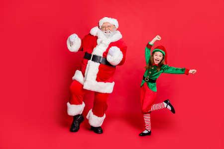 Foto de cuerpo entero de dos emocionados Papá Noel con sombrero sombreros bailando en un evento festivo vistiendo un traje verde brillante aislado sobre fondo rojo.