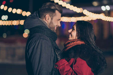 Photo of two sweethearts pair in love attending city park at newyear midnight standing opposite wearing warm winter jackets outdoors