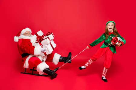 Foto de tamaño completo de Papá Noel divertido con anteojos anteojos y elfo lindo en sombreros de sombrero verde sosteniendo trineos llevan bolsa de saco con regalos aislados sobre fondo rojo