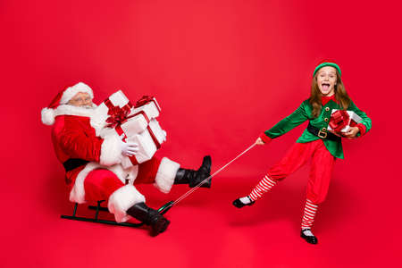 Full size photo of funny santa claus with eyeglasses eyewear spectacles and cute elf in green hat headwear holding sledges carry sack bag with gifts isolated over red background