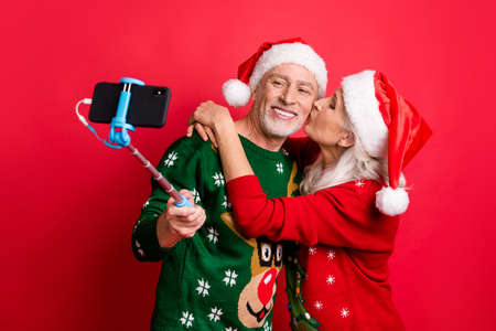 Blogging time social media concept. Photo of two romantic dreamy grey white haired sweethearts people married spouses making picture on cell using monopod hugging kissing in cheek isolated background Reklamní fotografie