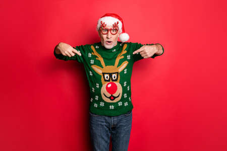Did you see this. Photo of cheerful excited bearded grey-haired guy showing rudolf with red nose on his funky style december green retro knitted jumper pullover isolated bright color background Stock fotó