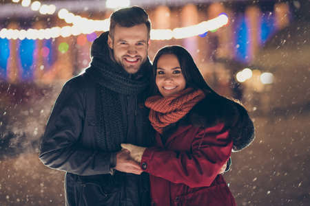 Photo of two people visiting central city park at x-mas eve standing close wearing warm winter jackets and scarfs feel holiday spirits outdoors