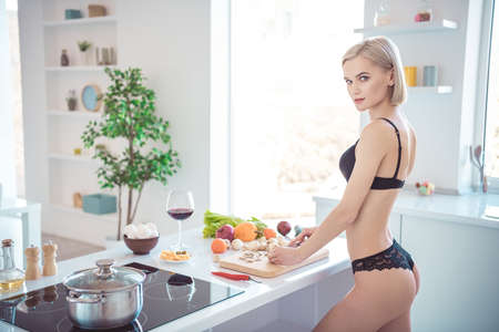 Profile side view of her she nice-looking attractive adorable stunning sporty girl making healthy fresh homemade tasty yummy dish salad in modern light white interior kitchen indoors 免版税图像