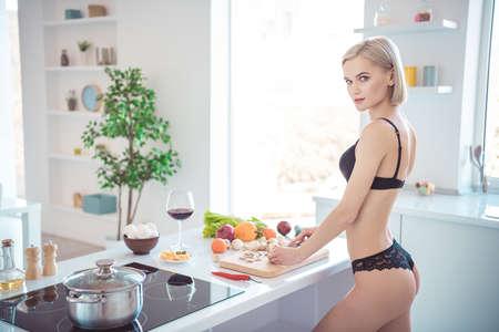 Vue latérale du profil d'elle, elle, jolie, jolie, adorable, superbe, sportive, faisant une salade de plats délicieux faits maison et sains dans une cuisine intérieure blanche et moderne à l'intérieur