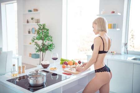 Profilseitenansicht von ihr hübsch aussehendes, attraktives, sportliches Mädchen, das ein gesundes frisches hausgemachtes leckeres leckeres Gericht in einer modernen hellweißen Innenküche im Innenbereich zubereitet