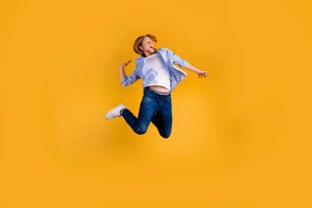 Full body photo of crazy redhead guy jumping high making slam dunk trick best basketball team player final cup game wear casual outfit isolated yellow background Фото со стока