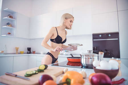 Photo of half naked model lady cooking breakfast checking nice smell omelet on frying pan closing eyes wearing underwear bra lace panties standing in light kitchen
