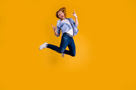 Full length photo of crazy redhead guy jumping high making horns with fingers excited to visit favorite band concert wear casual outfit isolated yellow background