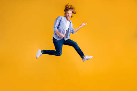 Full length body size photo of crazy funny red haired rock hard rocker man fan wearing jeans denim checkered blue shirt sneakers pretending to play guitar jumping isolated vivid color background