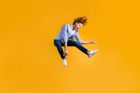 Full length body size photo of crazy red haired rock playing guy musician fan wearing jeans denim checkered blue shirt sneakers pretending to play guitar jumping isolated vivid color background