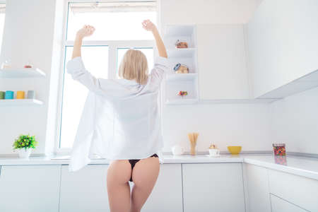 Rear back behind view of her she nice-looking attractive lovely pretty sportive graceful juicy perfect figure girl stretching waking up in modern light white interior kitchen house hotel room