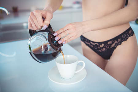 Cropped close-up view of her she naked nude attractive sporty girl pouting coffee porcelain cup in modern light white interior kitchen house indoors