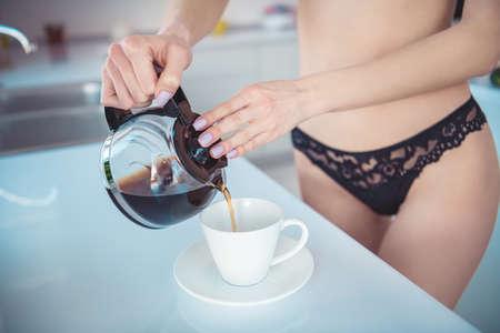 Vista cercana recortada de ella ella atractiva chica deportiva haciendo pucheros taza de porcelana de café en casa de cocina interior blanca luz moderna en el interior