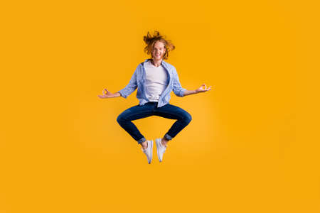 Full length photo of redhead handsome guy jumping high meditating exercise holding body in lotus position wear casual trendy clothes isolated yellow background