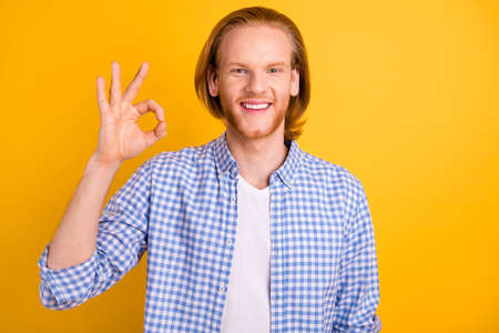 Photo of cheerful cute handsome creative guy showing you ok sign wearing blue shirt smiling beaming toothily isolated over bright color background Фото со стока