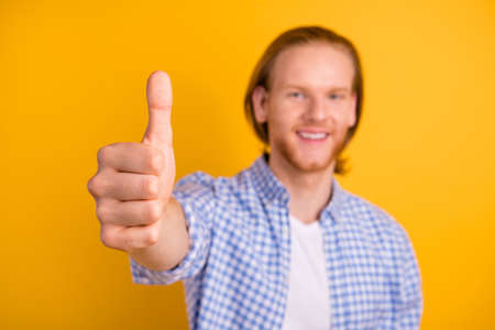 Close up photo of cheerful man showing you thumb up sign emphasized isolated over yellow vivid color background Stockfoto - 130571203