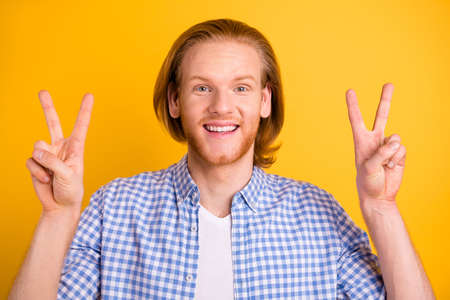 Close up photo of cheerful kind friendly nice cute handsome employee excited about being accepted to job showing you double v-sign isolated over yellow vibrant color background