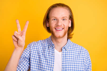 Close up photo of cheerful crazy handsome man smiling toothily showing you v-sign wearing checkered clothes isolated over vivid color background Фото со стока