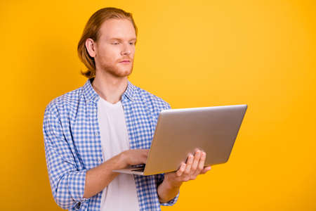 Photo of working serious concentrated business man holding laptop with his hands analyzing two sources of information looking into screen intently