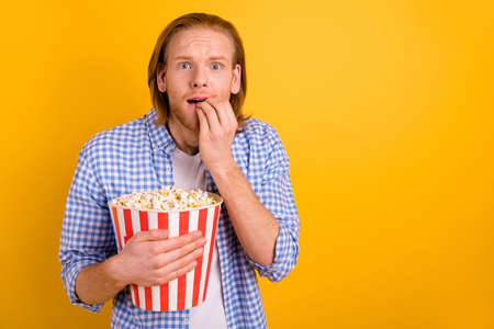 Photo of terrified speechless scared resting man in panic while watching horror movie at cinema with empty space next to him isolated over yellow vivid color background Фото со стока